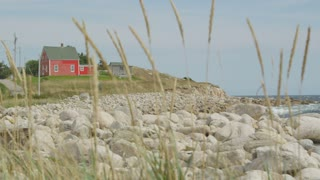 Red House Along Rocky Coast Through Tall Grass