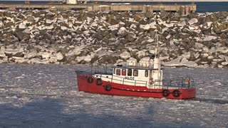 Red Pilot Boat Moving Through Icy Water