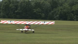 Red Striped Airplane Taxiing on Grass Field