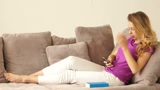 Relaxed young woman on sofa using mobile phone and smiling