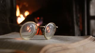 retro eyeglasses, open book and fireplace