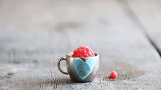ripe raspberry in a cup with heart, place for text