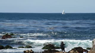 Rocky Ocean Shore With Sightseers And Sailboat