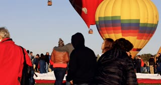 Romantic couple embracing while watching hot air balloons