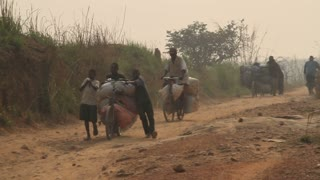Rough Dirt African Road With Bicyclists Pushing Cargo