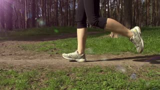Runner feet running on a rural road closeup. Woman fitness sunrise jog workout welness concept. Slow motion. Filmed at 250 fps.
