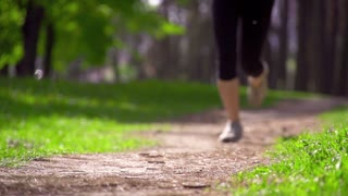 Runner feet running on a rural road closeup. Woman fitness sunrise jog workout welness concept. Slow motion. Filmed at 250 fps.