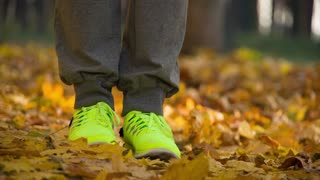 Runner woman feet running on autumn road closeup on shoe. Female fitness model outdoors fall jog workout on a road covered with fallen leaves. Sports healthy lifestyle concept. Slow motion 120fps 4k