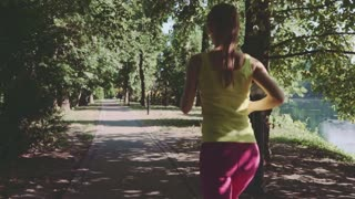 Runner woman running in park exercising outdoors. Steadicam stabilized shot. Sportswoman wearing fitness tracker bracelet while training in the park. Slow motion. Lens flare.