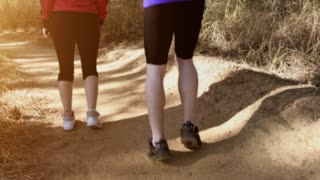 Running couple on a trail at sunrise, close up shoes steadicam shot