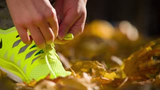 Running shoes. Barefoot running shoes closeup. Female athlete tying laces for jogging on road in minimalistic barefoot running shoes. Runner getting ready for training. Sport lifestyle. Slow motion.