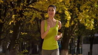 Running woman. Runner is jogging in sunny bright light in the autumn park background. Female fitness model training outside on a warm fall day and listening to music. Sport lifestyle. 4k slow motion.
