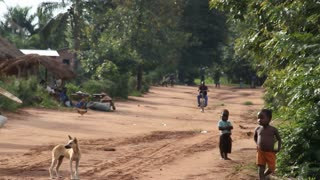 Rural Dirt Road In Africa With Children Dogs And Bicycles