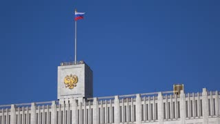 Russian flag and state emblem on the top of the government house in Moscow, 4K