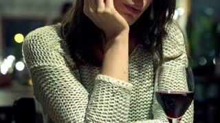 Sad beatiful woman drinking wine in bar late at night