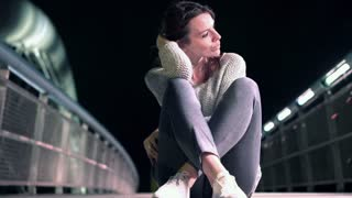 Sad beautiful woman looking sitting on the bridge at night