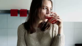 Sad, pensive woman drinking juice in kitchen