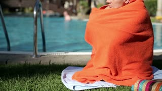 Sad woman in red towel sitting by the swimming pool, tilt up down