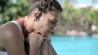 Sad woman listening music by the swimming pool