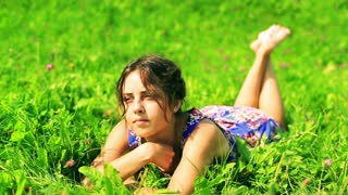 Sad woman lying on green meadow and wearing beautiful dress