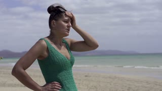 Sad woman standing alone on the beach, slow motion shot at 240fps