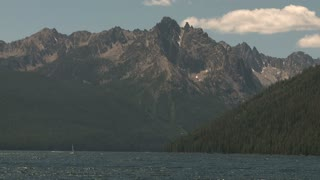 Sailboat on Lake in Front of Snow Speckled Rocky Mountain Peak