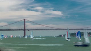 Sailfishes on the Tagus river with 25th of April Suspension Bridge on background, connecting Almada and Lisbon in Portugal timelapse with cloudy blue sky 4K wide angle lens