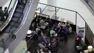 SAINT-PETERSBURG - May 12:  People eat in the cafe and go up and down on the escalator in trade center on May 12, 2013 in Saint-Petersburg, Russia.