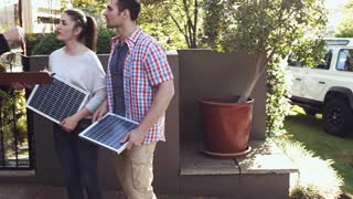 Salesman selling solar panel to young couple home owners to save power or electricity consumption.