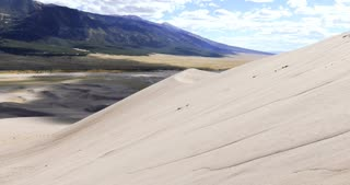 Sandboarding down huge sand dune in Great Sand Dunes National Park