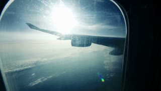 Scenic view from illuminator while traveling by air. Plane wing with sun flare and clouds beneath