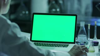 Scientist is using Laptop with Green Screen in Laboratory. Great for Mock-up Usage.