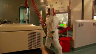 Scientists In Bubble Suits Work In Laboratory