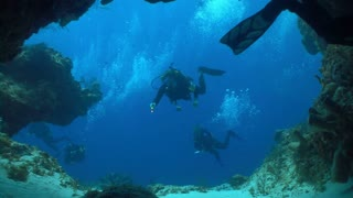Scuba Divers Swimming Into Underwater Cave
