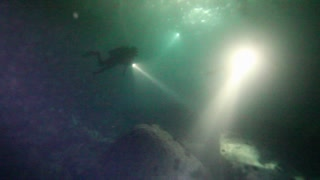 Scuba Divers Using Flashlights Underwater