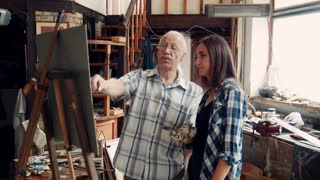 Senior Artist And young Woman painting on canvas using oil paint. He teaches young girl how to draw