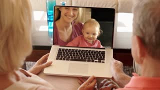Senior couple enjoying video online with daughter and grandchild.