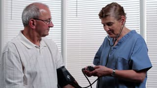 Senior man getting blood pressure checked by nurse