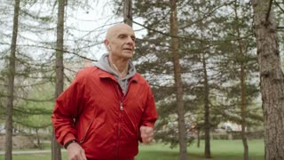 Senior man running in the park and listening to music on headphones