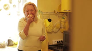 Senior woman eating apple in the yellow kitchen and looking to the camera.