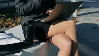Serious businesswoman talking on cellphone and working outside, steadycam shot