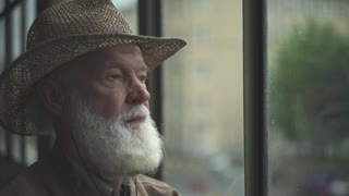 Serious senior man with a white beard and wearing a hat looking out the window