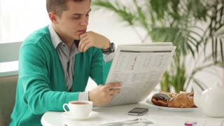 Serious young man sitting at table reading newspaper looking at camera and turning back to reading. Panning camera