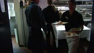 Server Brings Out Food Into Busy Restaurant