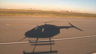 Shadow Of Helicopter Hovering Over Airport Runway