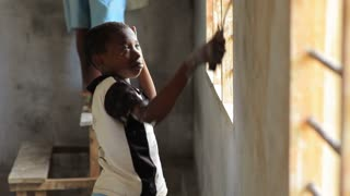 Shot of Child Painting the Inside of a Building