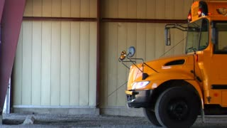 Shot Of Empty Schoolbus Pulling Out Of Garage