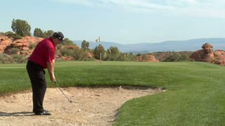 Shot Of Golfer Chipping Out Of Sand Trap Onto Green