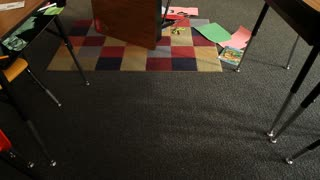Shot Of Knocked-over Desk And Chair In Classroom