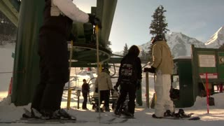 Shot Of Skiiers And Snowboarders At Chairlift Base